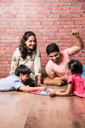 Indian young family of four playing board games like Chess, Ludo or Snack and Ladder at home in quarantine