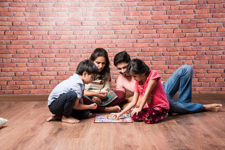 Indian young family of four playing board games like Chess, Ludo or Snack and Ladder at home in quarantine Stock Photo