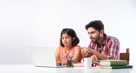 Cute Indian girl with father studying or doing homework at home using laptop and books - online schooling concept