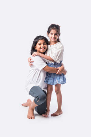 Cute little Indian asian siblings standing and embracing each other in white clothes while standing againstwhite background.