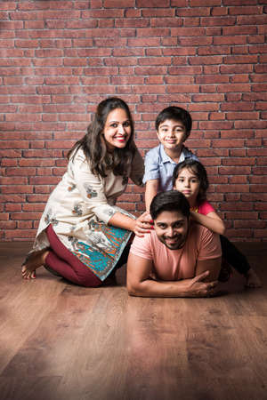 Happy Indian girl and boy playing riding on back or piggyback with father, indoor shot with mother looking