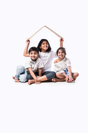 Indian kids holding 3D paper house model - showing Craft or real estate concept