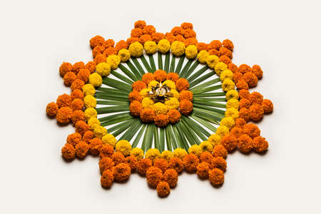 Flower Rangoli for Diwali or Pongal Festival made using Marigold or Zendu flowers and Rose petals over moody or white background, selective focus