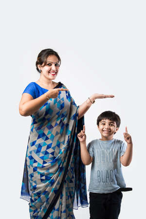 Smiling Attractive Indian Woman in saree Showing Copyspace against white background Imagens