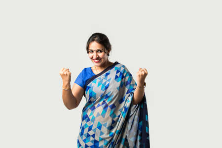 Portrait of successful pretty Indian young woman in sari or saree, with hands folded or thumbs up, isolated against white background