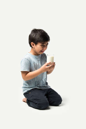 Indian kid crying while holding milk glass or for milk
