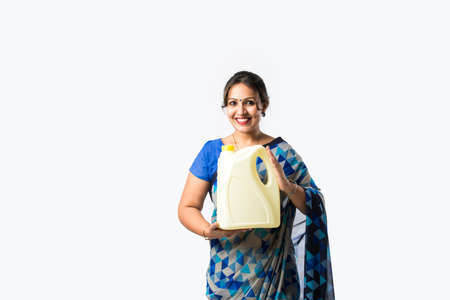 Indian woman in saree presenting plastic bottle, can or container white standing against white background