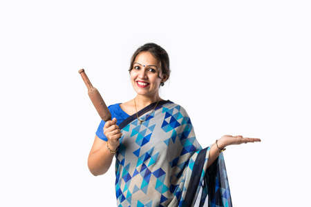 Portrait of an Indian asian woman in saree in kitchen, holding wooden ladle, belan, spatula or pan, isolated against white background