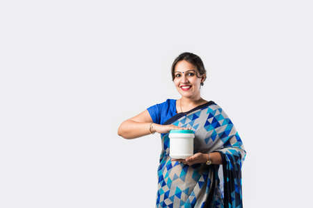 Indian woman in saree presenting plastic bottle, can or container white standing against white background Banque d'images