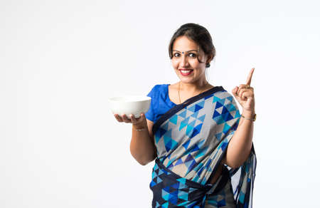 Indian asian woman or housewife in sari or saree holding or presenting white ceramic plate or bowl