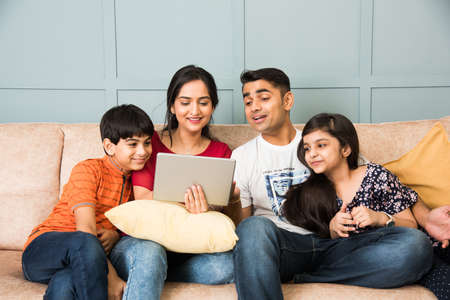 Indian family sitting on sofa and using smartphone, laptop or tablet, watching movie or surfing internet Banco de Imagens