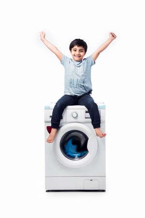Indian happy Small boy posing with Washing Machine or Dishwasher against white background