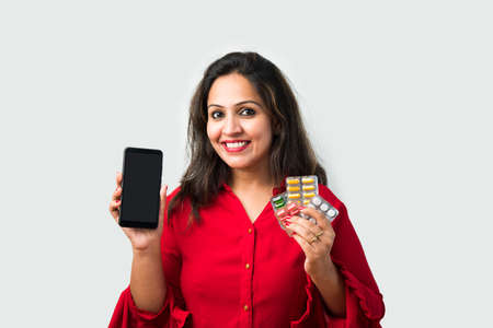 Medicine. Beautiful Smiling Indian asian Woman Holding Blister Pack With Pills In Hand. Asian Girl With Tablets showing mobile screen Reklamní fotografie