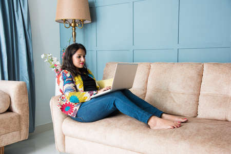 Asian Indian pretty girl or woman using laptop or tablet for chatting, online meeting, surfing or streaming movies, sitting on sofa 版權商用圖片
