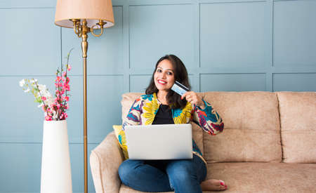 Indian pretty woman or girl using debit or credit card for online shopping on laptop computer