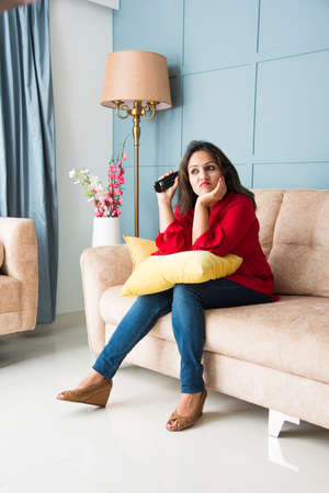 Indian asian woman got bored watching TV surfing channels but finding nothing interesting to watch, sitting on sofa or couch