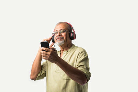 happy senior Indian asian bearded man smiling using headphones with smartphone or tablet against white background, presenting screen or dancing