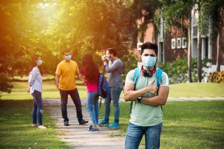Asian Indian students wears face mask and follow social distancing norms in college or university campus after corona Pandemic unlock, focus on one student Stock Photo