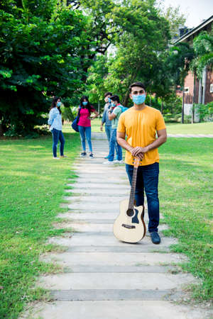 Asian Indian students wears face mask and follow social distancing norms in college or university campus after corona Pandemic unlock, focus on one student Archivio Fotografico