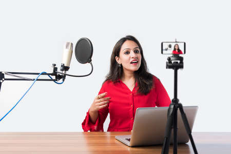 Pretty Indian woman speaks in front of microphone while recording a video blog for his subscribers, looking at camera