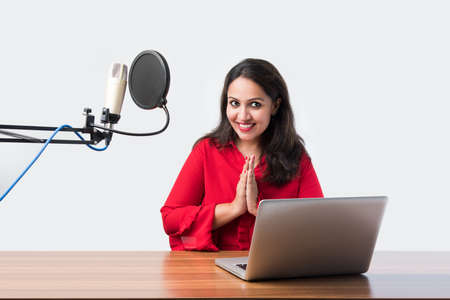 Pretty Indian woman speaks in front of microphone while recording a video blog for his subscribers, looking at camera Archivio Fotografico