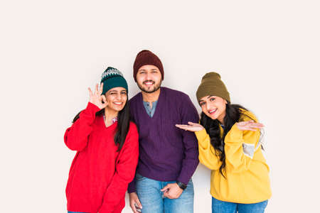 Indian asian young friends wears colourful and warm woollen sweaters and hats and pointing