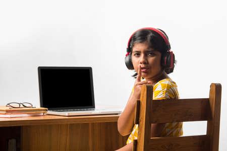 Cute Little Indian girl studying online using her laptop or Tablet computer at home or attending school during corona pandemic or lockdown Foto de archivo