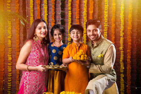 Diwali or Rakshabandhan Celebration - Indian young family of four celebrating Deepavali or bhai Dooj festival with sweet laddoo, oil lamp or diya and gift boxes, eating food or taking selfie