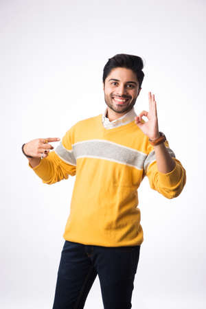 Indian handsome man wears winter wear or woolen sweater, presenting or showing. Standing against white background