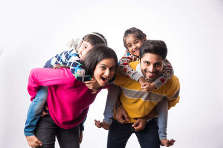 Asian Indian young family wears sweater or warm woolen or woollen winter cloths, standing isolated against white background