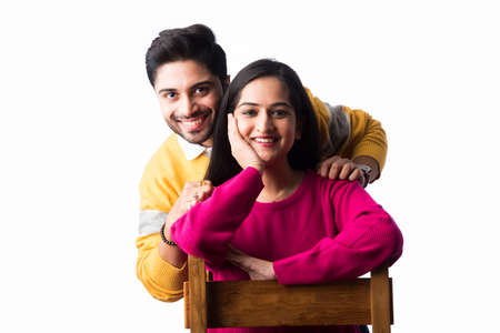 Asian Indian couple wears colourful warm sweater or woolen winter cloths, standing isolated against white background