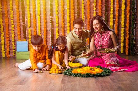 Indian family lighting or arranging oil lamp or diya around flower rangoli on diwali festival night