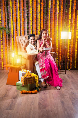 Indian attractive couple in traditional wear celebrating Diwali Festival, Birthday or Anniversary with surprise gifts and sweet laddoo against decorated background with marigold flowers