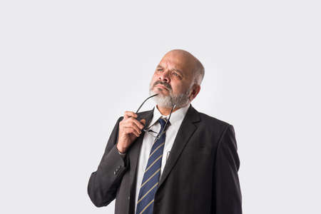 Pensive thoughtful Indian old businessman. Touching chin. Asian senior bald and bearded business person thinking against white background