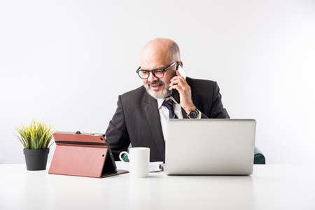 Asian Indian senior financial businessman sitting at his workstation or desk in front of a computer, laptop and tablet. Speaking on phone while doing some paperwork Archivio Fotografico