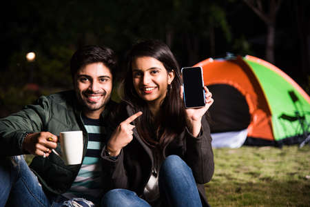 Happy young asian indian couple camping, sitting by tent at campsite relaxing and drinking tea.