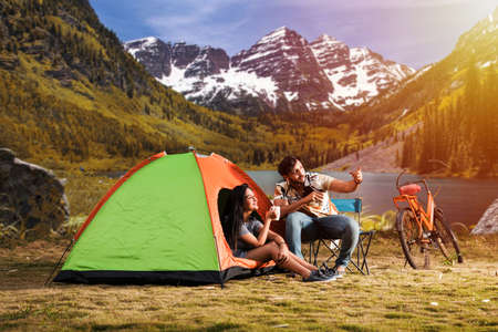 Happy young asian indian couple camping, sitting by tent at campsite relaxing and drinking tea. Zdjęcie Seryjne