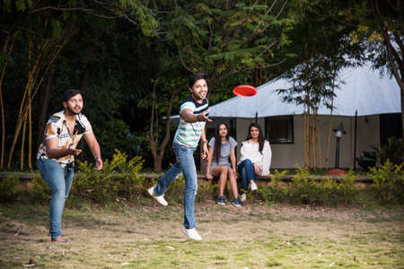 Group of Indian asian young people or friends in casual wear playing frisbee or disk throwing while spending carefree time outdoors Archivio Fotografico