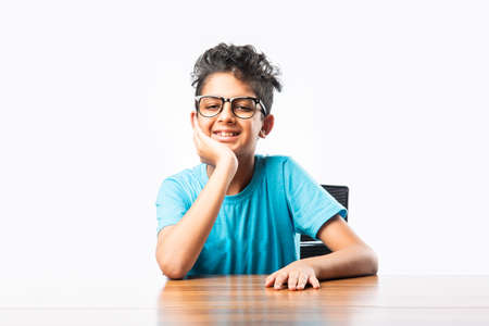 Indian asian boy or male child sitting at table or desk, looking at cemara, thinking or pointing something