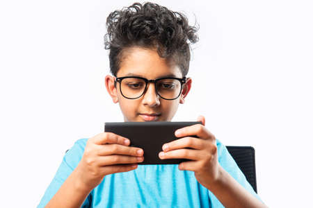 Indian asian small boy or kid using smartphone for gaming or for education