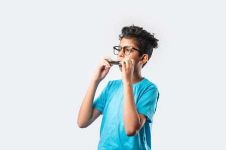 Indian asian little boy playing harmonica or mouth organ, early learning concept