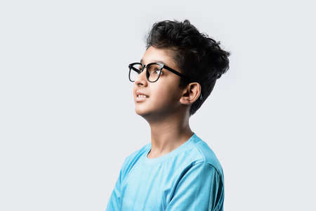 Portrait of cheerful Indian asian little boy with spectacles celebrating success standing against white background