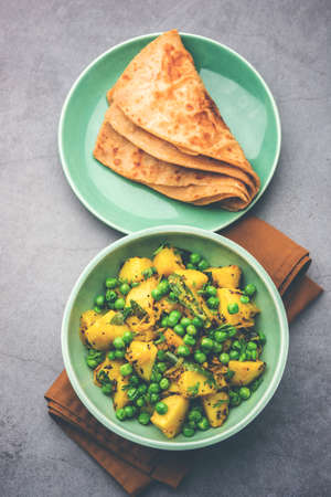 Aloo Mutter or Matar aalu dry sabzi, Indian Potato and green Peas fried together with spices and garnished with coriander leaves. served with roti or chapati Banque d'images