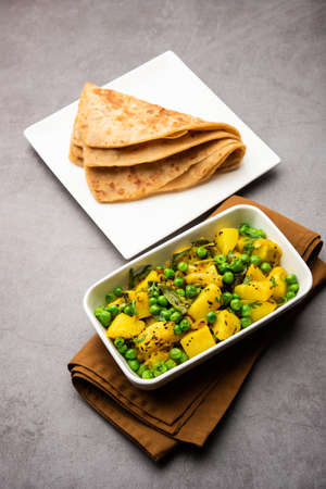 Aloo Mutter or Matar aalu dry sabzi, Indian Potato and green Peas fried together with spices and garnished with coriander leaves. served with roti or chapati