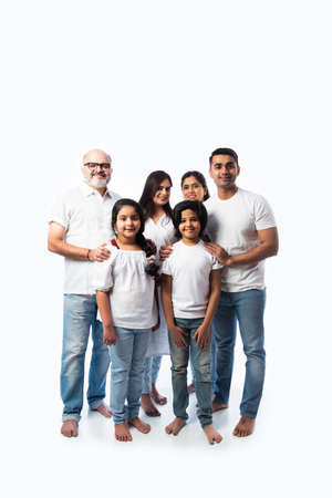 Indian multigenerational family in white cloths standing and looking at camera against white background