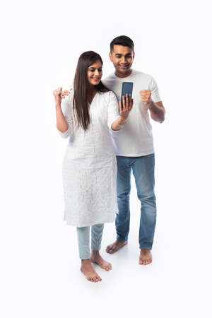 Indian asian young couple using smartphone against white background
