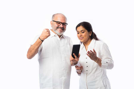 Happy Indian senior couple using smartphone. Standing isolated against white background