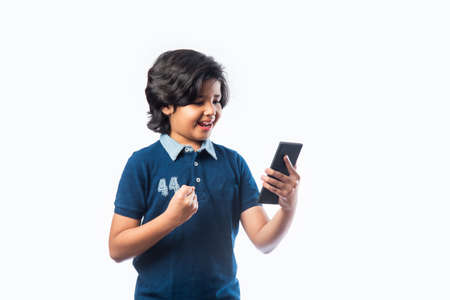 Indian kid using smartphone or mobile phone while wering glasses, with success or sad expressions