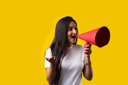 Indian young girl with megaphone made out of paper. Announcing, screeming or advertising while standing against yellow studio background Imagens