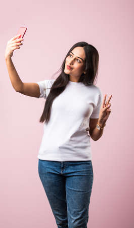 Pretty millennial indian girl isolated on pink studio background text messaging on cell phone or using smartphone with wireless connection